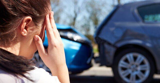 Lady looking at her car after an accident
